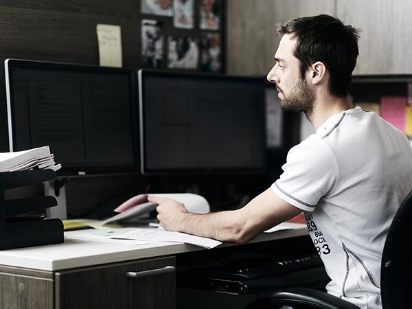 Jeune homme assis à son poste de travail